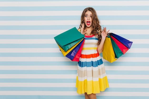 Mujer asombrada de cabello castaño con rizos y ojos azules asombrada por los vestidos que ve en la ventana. retrato de niña sorprendida posando con bolsas de colores en la pared rayada