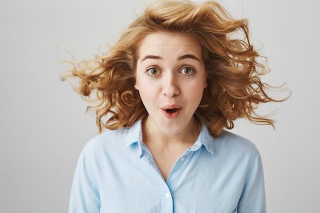 Mujer asombrada con cabello rizado flotando en el aire