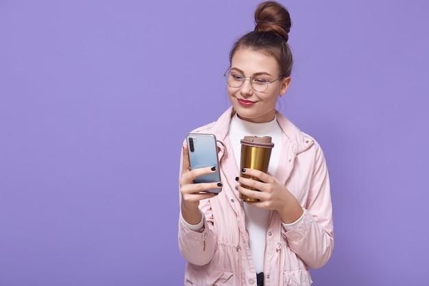 Mujer de aspecto agradable con gafas y chaqueta rosa pálida posando aislada sobre una pared lila, bebiendo bebidas calientes de una taza termo, sosteniendo el teléfono inteligente en las manos y navegando por internet.