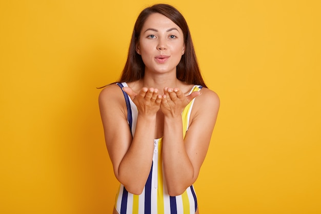 Mujer de aspecto agradable con piel sana, vestido con traje de baño, haciendo un gesto de beso al aire, coquetea con un chico guapo en la playa, aislado en amarillo. concepto de personas