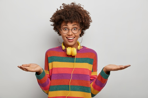 Mujer de aspecto agradable que levanta ambas palmas, sostiene espacio para copiar, tiene una expresión amigable, usa anteojos, suéter informal, mira directamente a la cámara, usa auriculares