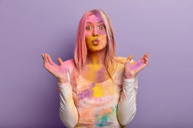 Una mujer de aspecto agradable tiene los labios doblados, extiende las manos, viste ropa informal, tiene una expresión alegre, está sucia con polvos de colores, aislada sobre una pared lila. el polvo de colores explota