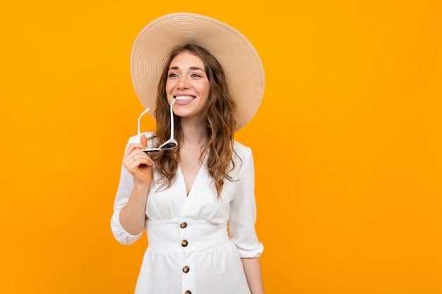 Mujer de aspecto europeo en un sombrero de paja sobre un fondo de una pared amarilla, tiene gafas de sol en sus labios