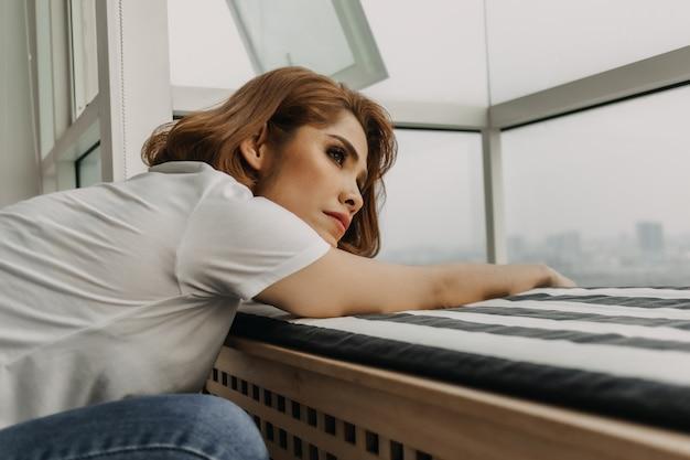 Mujer de aspecto fresco está descansando y mirando la vista desde su apartamento