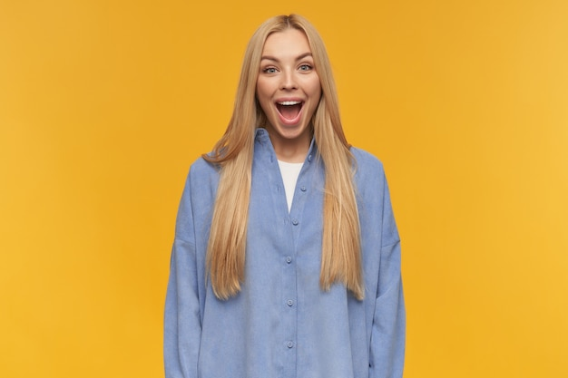 Mujer de aspecto positivo, chica alegre con cabello largo y rubio. vistiendo camisa azul. concepto de personas y emociones. sonriendo ampliamente. mirando a la cámara, aislada sobre fondo naranja
