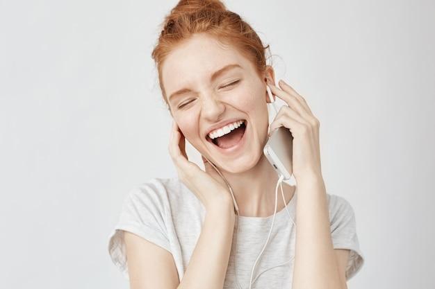 Mujer astuta alegre regocijo escuchando música en auriculares sonriendo.