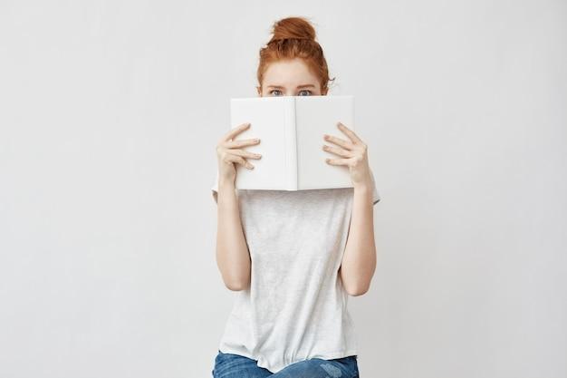 Mujer astuta escondiendo la cara detrás del libro.