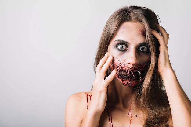 Mujer asustada con la cabeza tocando la cara dañada