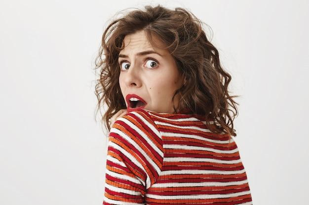 Mujer asustada y conmocionada se vuelve hacia la cámara, jadeando de miedo