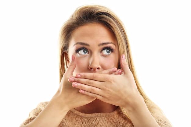 Mujer asustada mirando a la cámara aislada sobre un fondo blanco.