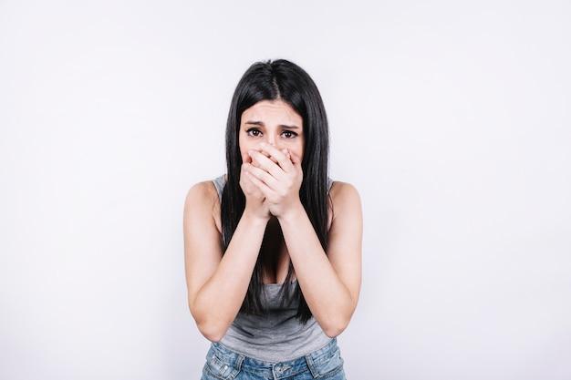 Mujer asustada que cubre la boca