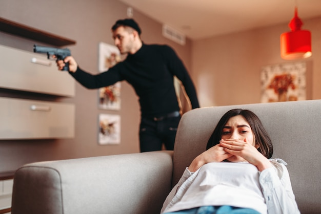 Mujer asustada que se esconde en el sofá contra el asesino en ropa negra con pistola en las manos. gángster penetró en el apartamento. robo a domicilio
