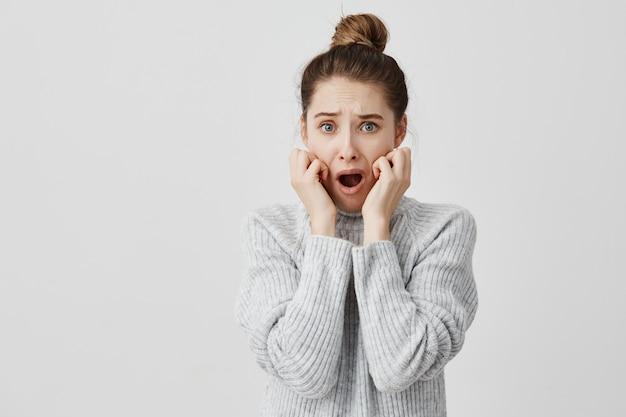Mujer asustada en suéter gris sosteniendo su mano en las mejillas con la boca abierta aterrorizada. diseñador gráfico femenino preocupado por falta de plazo. concepto de violación