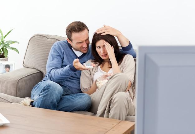 Mujer asustada viendo una película de terror con su novio