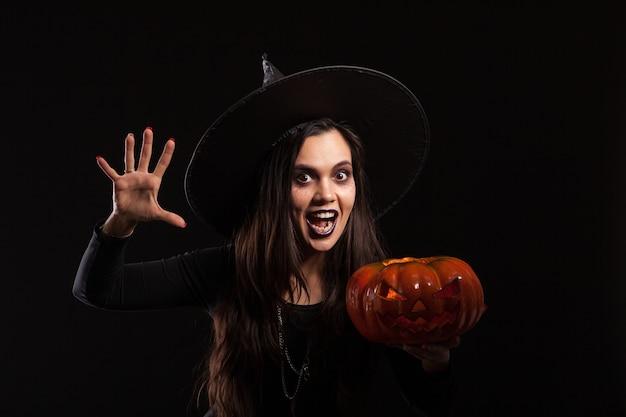 Mujer asustadiza vestida como una bruja con un gran sombrero para halloween sosteniendo una calabaza. calabaza aterradora para halloween. vestido negro para halloween.