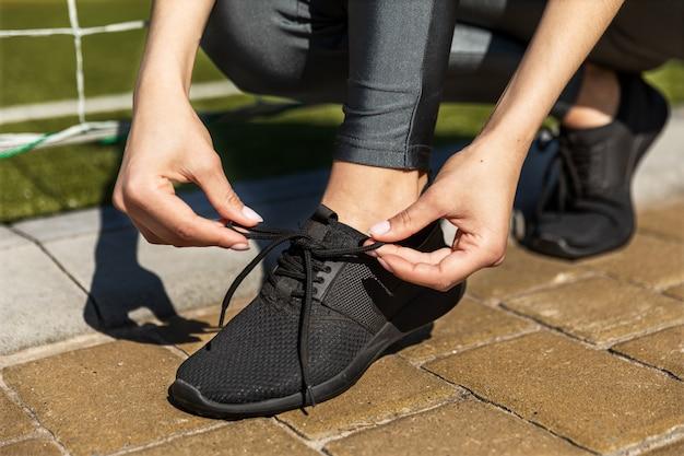 Mujer ata zapatillas de verano cerca de las puertas de fútbol