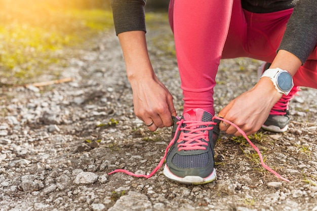 Mujer atando sus zapatillas grises