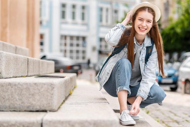 Mujer atando sus zapatos al lado de un edificio