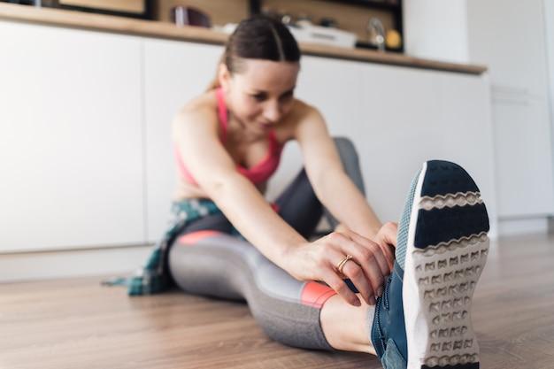 Mujer atando sus zapatos deportivos mientras está sentado en el suelo