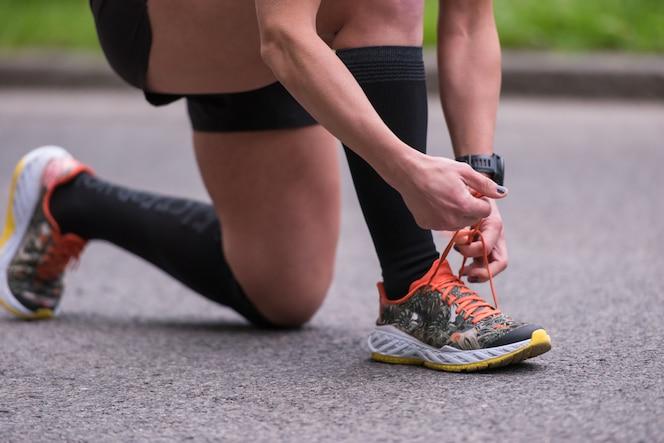 Mujer atar cordones de los zapatos de correr preparándose para correr en el parque de la ciudad en la mañana