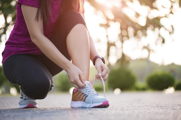 Mujer atar cordones de los zapatos listos para correr en el jardín