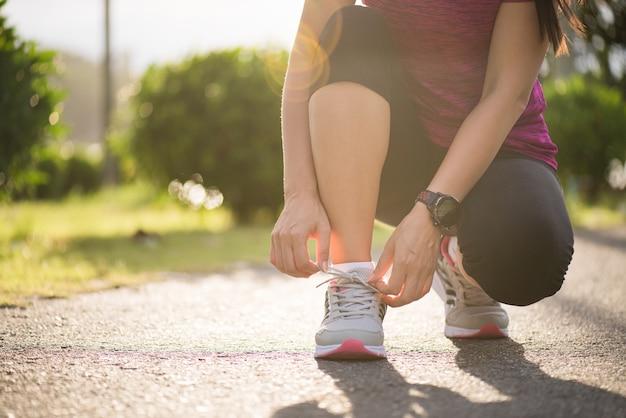 Mujer atar cordones de los zapatos, preparándose para correr en el fondo del jardín.
