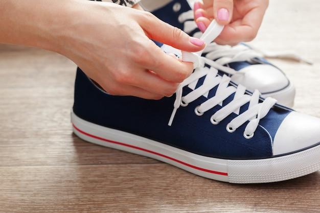Mujer atar cordones de los zapatos