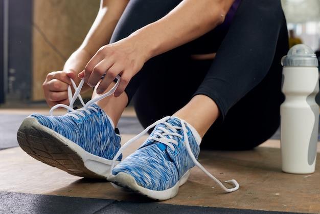 Mujer atar zapatos deportivos en el gimnasio