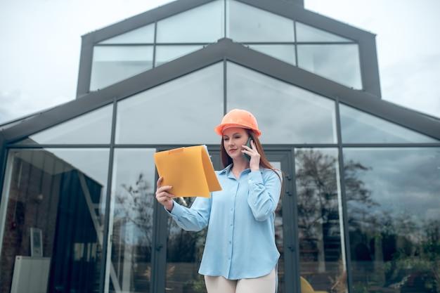 Mujer atenta con documento hablando por teléfono inteligente