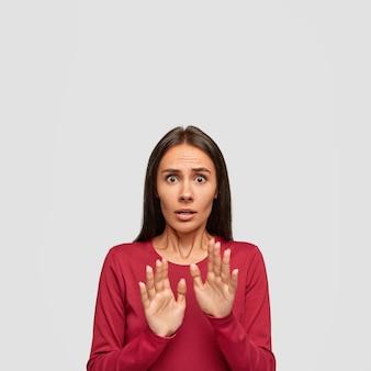Mujer aterrorizada ansiosa muestra señal de alto, se protege