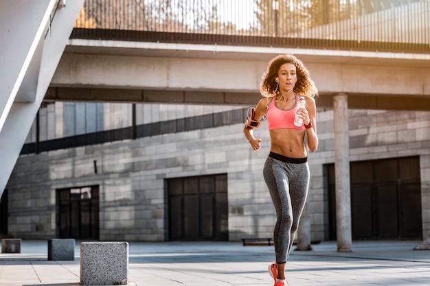 Mujer atleta. atractiva mujer rápida corriendo en el estadio mientras sostiene una botella de agua