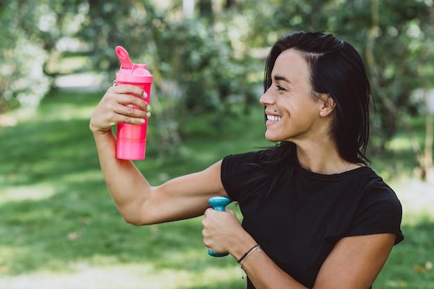 Mujer atleta con una gran pelota de fitness bebe proteínas de un agitador después del entrenamiento
