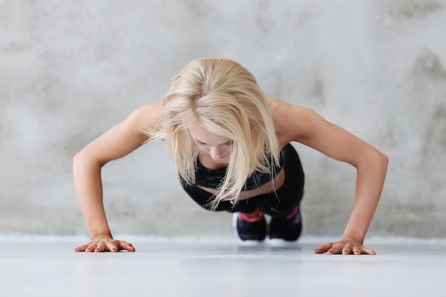 Mujer atleta musculoso haciendo flexiones