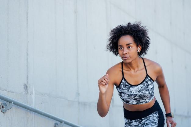 Mujer atlética afro corriendo y haciendo ejercicio al aire libre. concepto de deporte y estilo de vida saludable.
