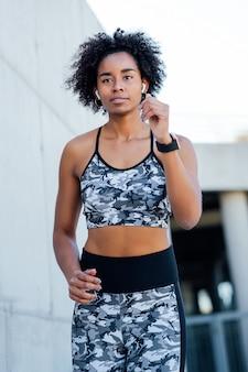 Mujer atlética afro corriendo y haciendo ejercicio al aire libre. deporte y estilo de vida saludable.