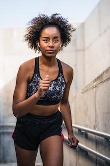 Mujer atlética afro corriendo y haciendo ejercicio al aire libre