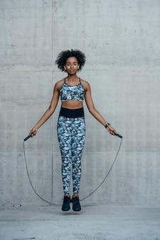 Mujer atlética afro haciendo ejercicio y saltando la cuerda al aire libre. deporte y estilo de vida saludable.
