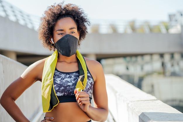 Mujer atlética afro con máscara facial y relajarse después de hacer ejercicio al aire libre en la calle