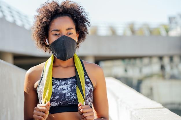Mujer atlética afro con mascarilla y relajarse después de hacer ejercicio al aire libre en la calle. nuevo estilo de vida normal. deporte y estilo de vida saludable.