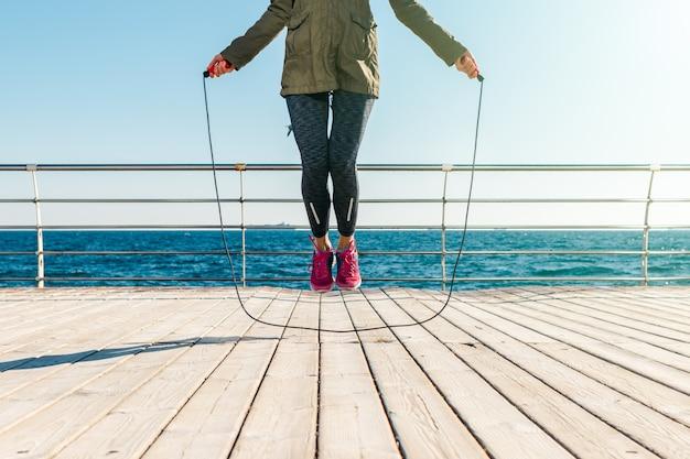 Mujer atlética en una chaqueta y zapatillas de deporte que saltan la cuerda por la mañana en la playa