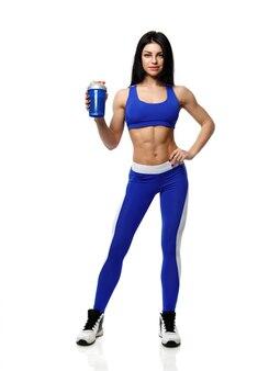 Mujer atlética con una coctelera en el fondo blanco
