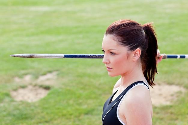 Mujer atlética concentrada dispuesta a lanzar la jabalina.