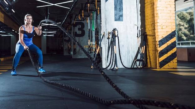 Una mujer atlética ejercita ingenio cuerdas de batalla en el gimnasio