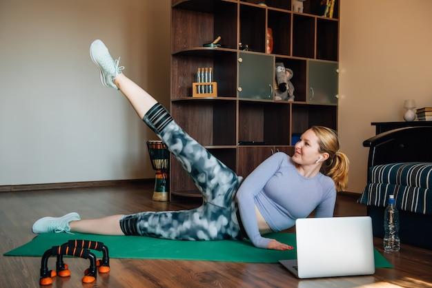 Mujer atlética entrenamiento en casa. la mujer joven hace ejercicios de fitness para las nalgas con un programa de entrenamiento en línea.