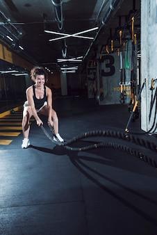 Mujer atlética feliz que ejercita con las cuerdas de la batalla en gimnasio