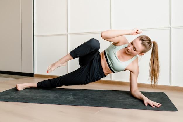 Mujer atlética haciendo ejercicio físico en casa en estera de yoga