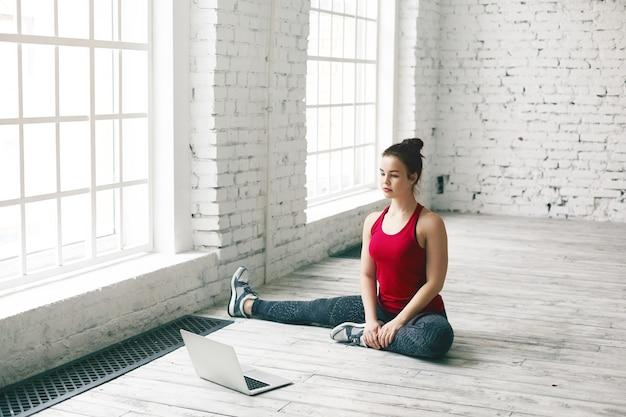 Mujer atlética joven con estilo en leggings, zapatillas y zapatillas para correr sentado en el piso en casa frente a una computadora portátil genérica abierta mientras ve el entrenamiento de yoga en línea, hace varias asanas, tiene una mirada seria