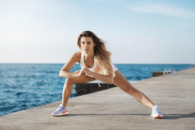 Mujer atlética joven hermosa activa que comienza el ejercicio matutino, que se extiende cerca del mar