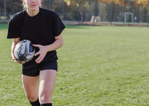 Mujer atlética manos sosteniendo una pelota de rugby