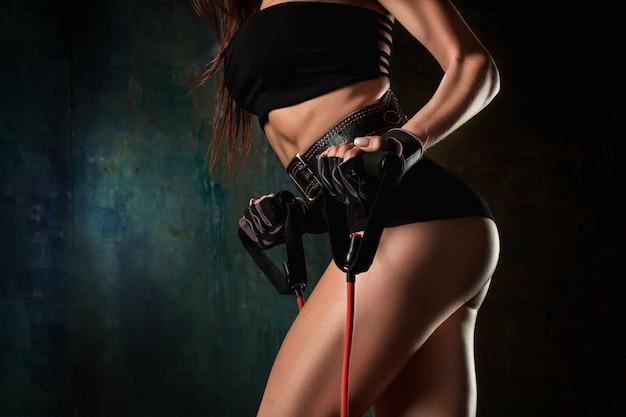 Mujer atlética morena que ejercita con la cinta de goma